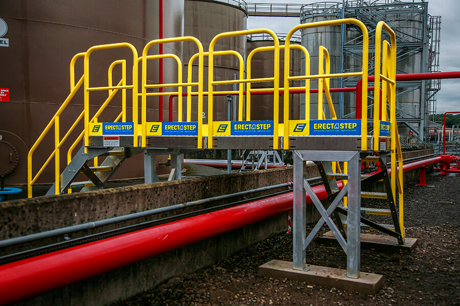 Metal Crossover Stairs With Platform and Handrails Above Pipe Outdoors