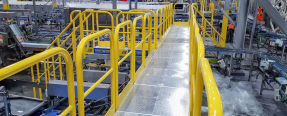 ErectaStep material handling conveyor crossover with punched tread aluminum platforms at the Nestle Waters facility in Ontario CA