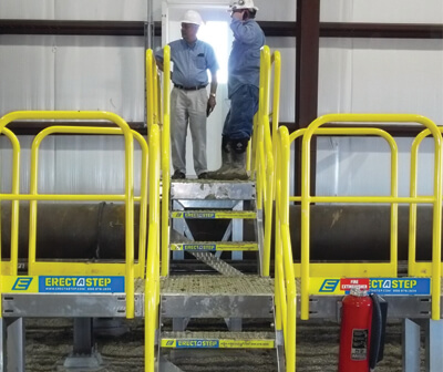 Two Workers Standing on Crossover Stairs Platform at Manufacturing Plant