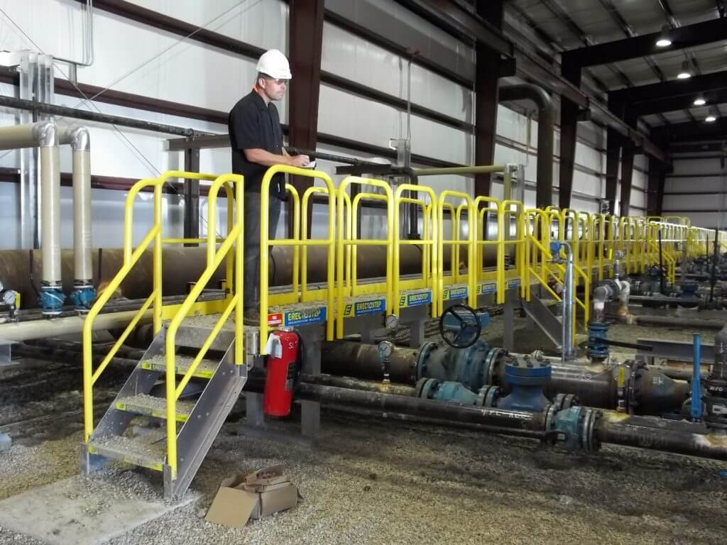 Working standing on long crossover stair installation over pipes